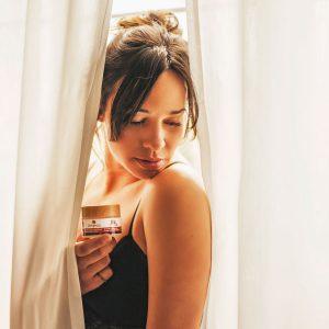 julia con crema facial Dehesia entre cortinas